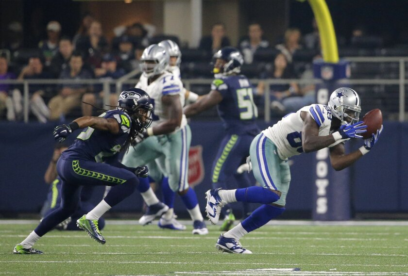 Seattle Seahawks cornerback Richard Sherman (25) watches as Dallas Cowboys' Dez Bryant (88) grabs a pass in the second half of an NFL football game Sunday, Nov. 1, 2015, in Arlington, Texas. (AP Photo/Brandon Wade)