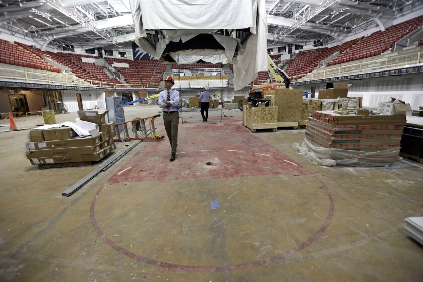 In this photo taken Thursday, May 26, 2016, deputy athletic director Michael Lipitz walks on the original basketball playing floor as contractors continue renovations to Reynolds Coliseum at North Carolina State University in Raleigh, N.C. (AP Photo/Gerry Broome)