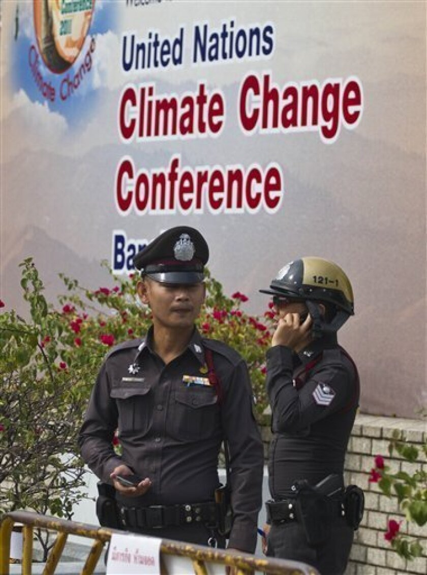 Bangkok police watch as religious leaders gather Friday, April 8, 2011 in Bangkok, Thailand, outside the United Nations Climate Conference to offer prayers and call on world leaders to reduce greenhouse gases and other emissions that damage the planet. (AP Photo/David Longstreath)