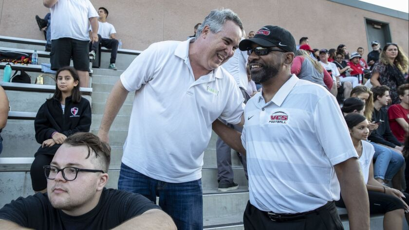 Former USC running backs coach Todd McNair chats with attorney Scott Carr before a game with the Village Christian Crusaders in Burbank on Friday.