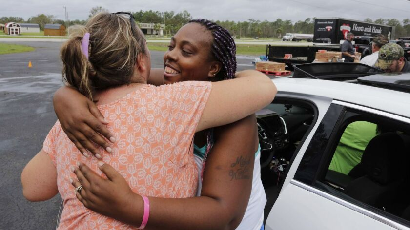 Shemika McCoo, right, embraces Kelly Shuler at Community Baptist Church in the aftermath of Hurricane Florence in Newport N.C. on Sept. 17.