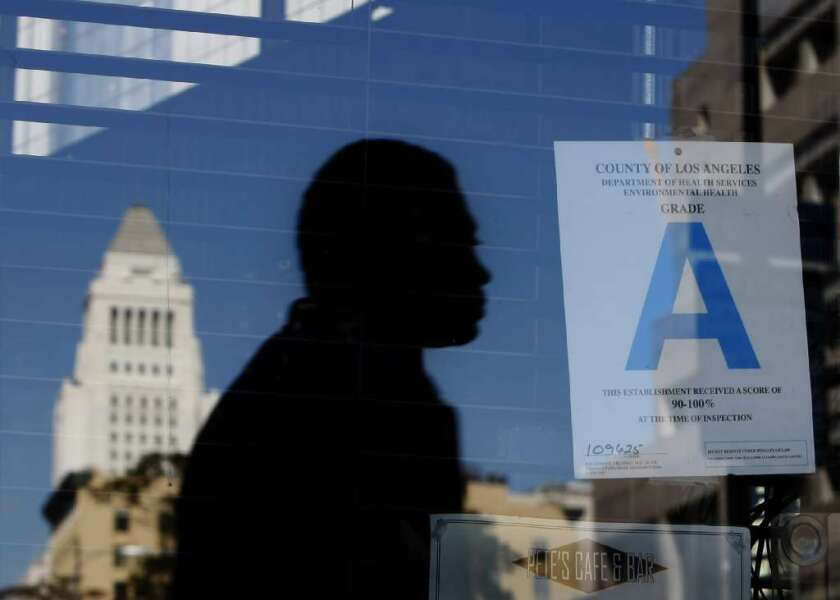 "A pedestrian and L.A. City Hall are reflected in the window of a downtown L.A. cafe, which displays an ""A"" restaurant grade."