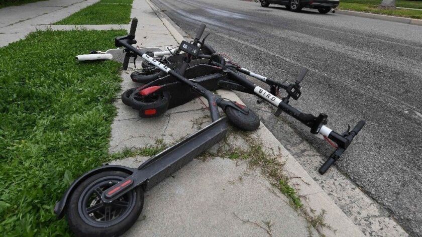 Electric scooters lie on a sidewalk in Los Angeles on Feb. 13.
