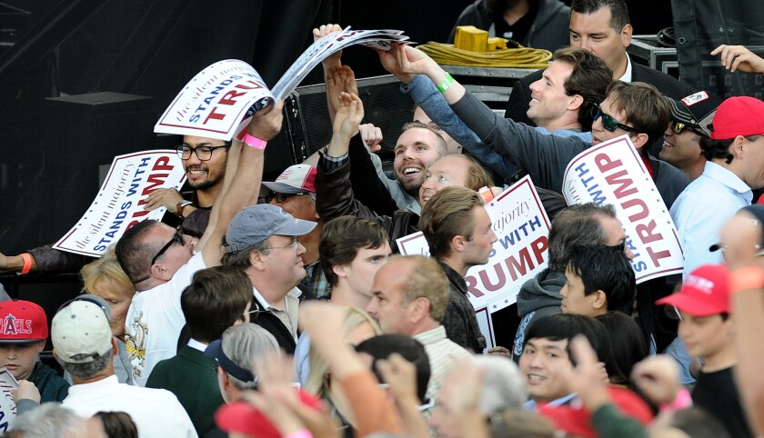 Trump supporters grab signs before a rally at the Orange County Fairgrounds in Costa Mesa.
