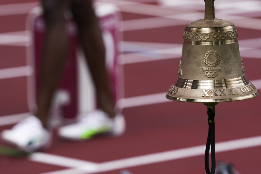 The bell hangs near the finish line at the Tokyo Olympic Stadium.