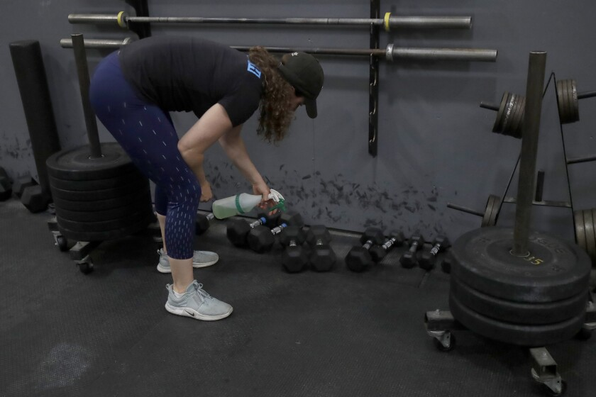 Alexis Garrod, CrossFit Potrero Hill partner and head coach, cleans off equipment in an empty gym in San Francisco.