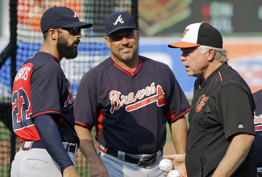 Atlanta Braves right fielder Nick Markakis, left, chats with Baltimore Orioles manager Buck Showalter, right, and Braves manager Fredi Gonzalez before an interleague baseball game between the Orioles and the Braves, Monday, July 27, 2015, in Baltimore. Markakis played his entire major league career with the Orioles before signing during the offseason with the Braves, who were in town Monday for the start of a three-game series. (AP Photo/Patrick Semansky)