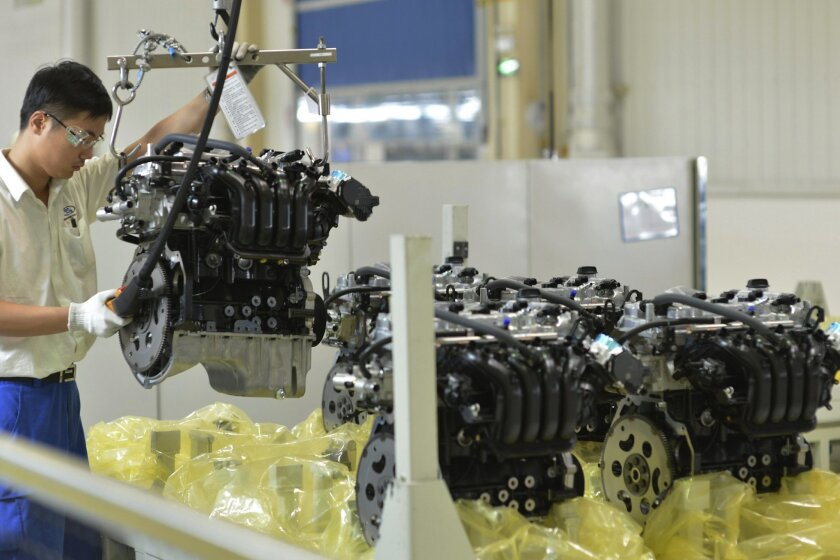 In this Tuesday, Sept. 23, 2014 photo, a worker arranges engine blocks at the General Motors assembly plant in Wuhan in central China's Hubei province. General Motors Co.'s main Chinese joint venture is recalling 2.2 million cars to deal with insufficient corrosion resistance on crankcase valves. The recall was ordered after Shanghai-GM received complaints about engine damage, according to the country's product quality regulator. The automaker is a joint venture between GM and state-owned Shanghai Automotive Industries Corp. (Chinatopix via AP) CHINA OUT
