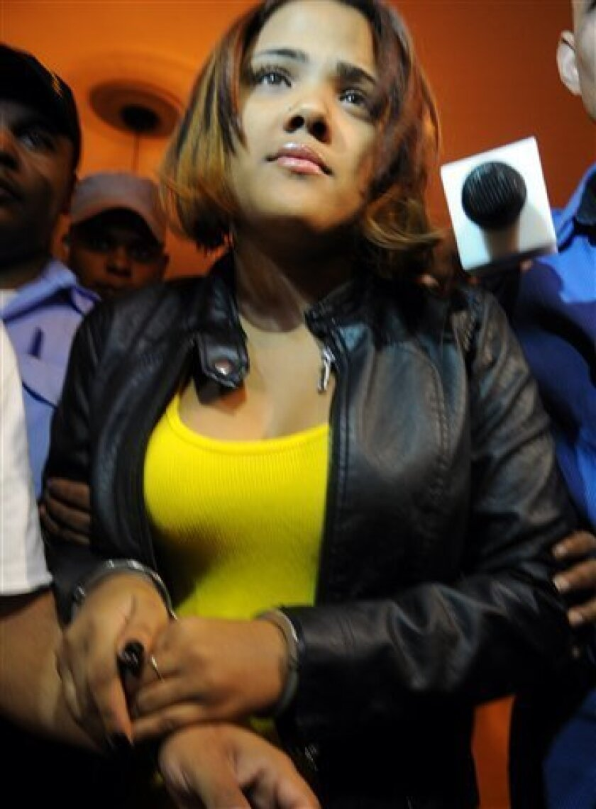 "Dominican Republic's singer Martha Heredia, is escorted handcuffed into the prosecutor's office in Santiago, Dominican Republic, Thursday, Feb. 21, 2013. Heredia, a winner of the TV talent show ""Latin American Idol"", was arrested late Wednesday and charged with drug smuggling after police found heroin stuffed in the heels of her platform shoes as she was about to board a plane to New York at the Cibao International airport in Santiago, according to National Drug Control Agency Director Frank Duran. (AP Photo)"