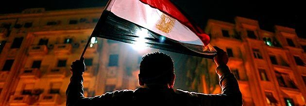 A man holds the Egyptian flag aloft in Tahrir Square after the announcement that President Hosni Mubarak would step down.