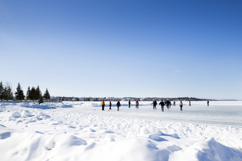 This undated photo provided by the Town of Sylvan Lake shows people playing hockey in Sylvan Lake, Alberta. Experts say and studies have shown fewer freezing days and less ice coverage in the winter over the past several decades. The future suggests it will become much more more challenging to maintain rinks on ponds and lakes. In places like Kingman and Sylvan Lake, Alberta, residents are keeping the tradition alive even if the skating season is shorter than it used to be. (Photo courtesy Town of Sylvan Lake via AP)