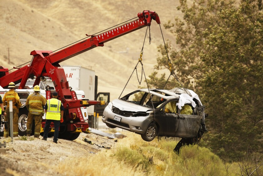 A heavy-duty tow truck retrieves a van in which six people died after it was struck by a big rig and burst into flames on the 5 Freeway near Gorman on Tuesday morning.
