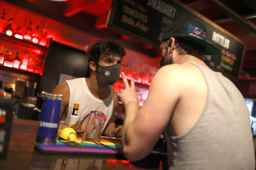 A bartender wearing a mask stands behind bar taking an order from a customer seated at the bar