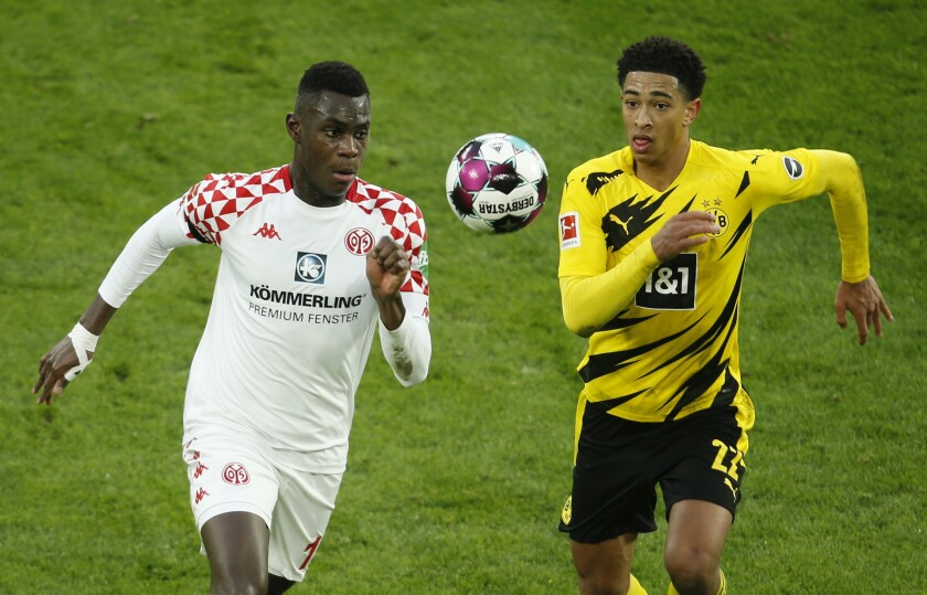 Moussa Niakhate of Mainz, left, in a duel with Dortmund's Jude Bellingham battle for the ball during the Bundesliga soccer match between Borussia Dortmund and FSV Mainz 05 at Signal Iduna Park in Dortmund, Germany, Saturday Jan. 16, 2021. (Leon Kuegeler/Pool via AP)