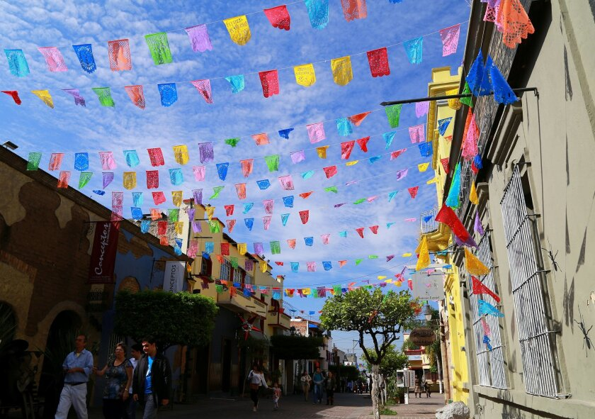 This picture taken Dec. 5, 2015, shows colorful bunting fluttering in the breeze along Independencia Avenue in Tlaquepaque, a historic suburb of Guadalajara, Mexico, known for its boutiques, galleries and restaurants commemorating Mexican independence. (Michelle Locke via AP)