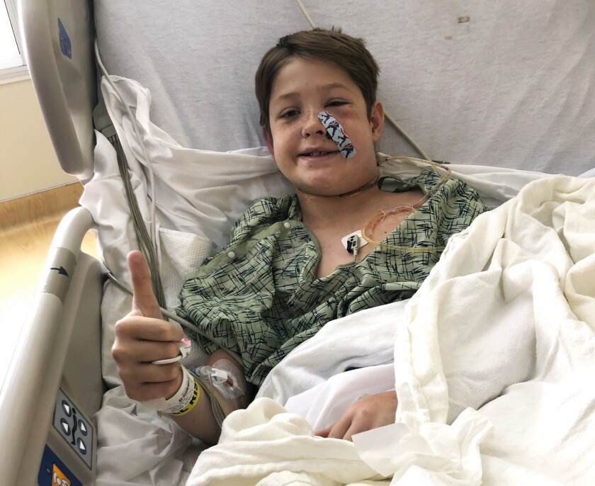Xavier Cunningham, of Harrisonville, Mo., gives a thumbs up while recovering at the University of Kansas Hospital in Kansas City, Kan., after surgery to remove a meat skewer that penetrated his skull from his face to the back of his head.