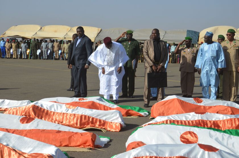 Niger President Mahamadou Issoufou bows near the bodies of military personnel at the Niamey air base on Friday. Niger's government has declared three days of mourning following an attack at a military base.
