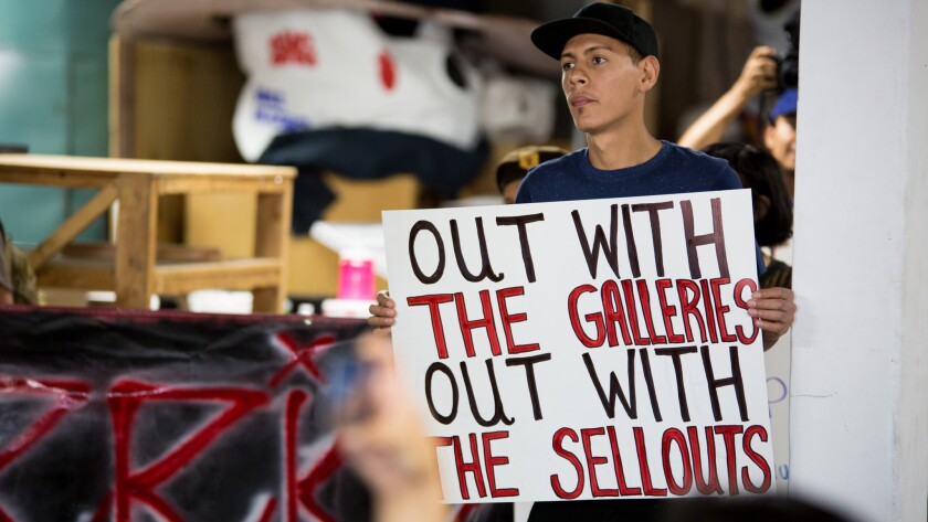 A member of an activist group holds a sign protesting Self Help Graphics and other art galleries in Boyle Heights.