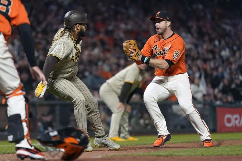 San Francisco Giants third baseman Evan Longoria, right, reaches to tag Fernando Tatis Jr.