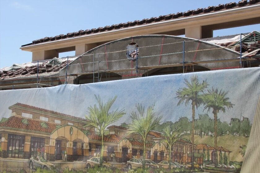 A rendering of the completed Palma de la Reina in front of the under-construction building. Photo by Karen Billing