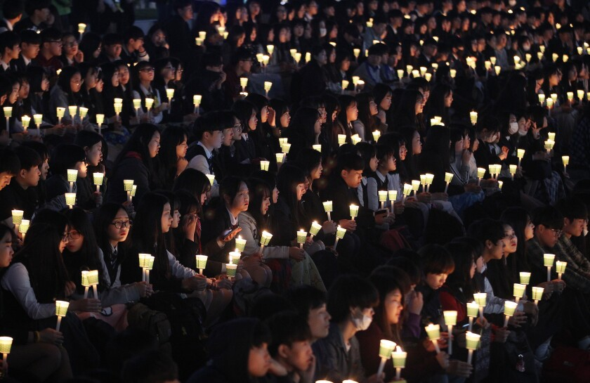 High school students hold candles to pay their respects to the victims of the Sewol ferry disaster during a ceremony April 15 on the eve of the sinking's two-year anniversary in Ansan, South Korea