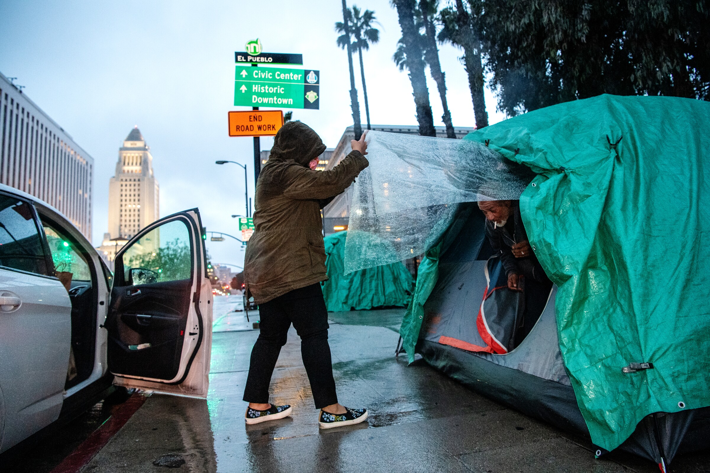 Melissa Acedera distributes meals and supplies to one of her contacts, Harvey, on Olvera Street on a rainy evening in downtown Los Angeles.