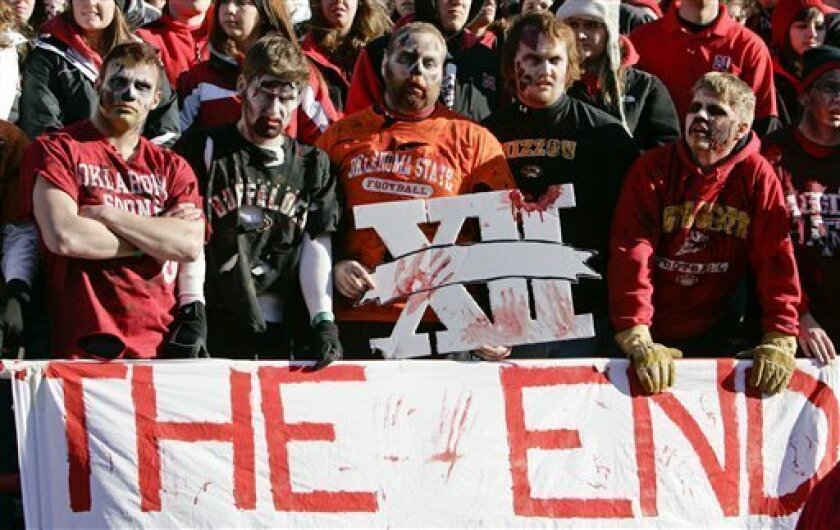 """Nebraska fans dress in jerseys of Big 12 teams and stand over a sign reading """"The End is Near"""", prior to Nebraska's last home game against a Big 12 conference foe, Colorado, in an NCAA college football in Lincoln, Neb., Friday, Nov. 26, 2010. (AP Photo/Nati Harnik)"""
