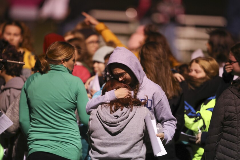 People attend a vigil for missing Wisconsin teen Jayme Closs at a football field in Barron, Wis.