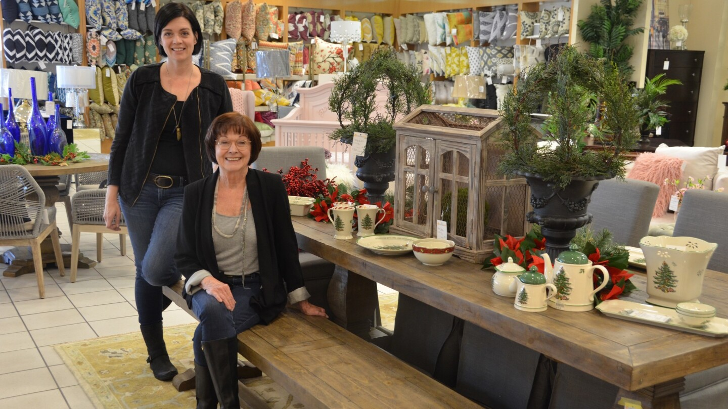 Furnishing Hope founder Beth Phillips, seated, and her daughter Robyn, who serves as program director, show one of the displays at the new Furnishing Hope store in Newport Beach.