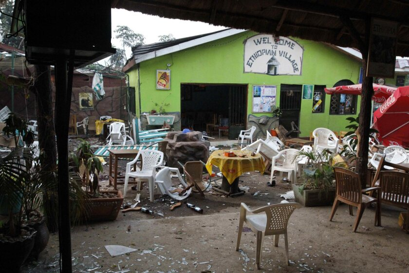 """FILE - In this Monday, July 12, 2010 file photo, damaged chairs and tables lie amongst the debris strewn after a bomb attack outside the """"Ethiopian Village"""" restaurant in Kampala, Uganda. A judge has convicted two men Thursday, May 26, 2016 of carrying out twin bombings in which more than 70 people were killed while watching the 2010 World Cup final in the Ugandan capital Kampala. (AP Photo/Marc Hofer, File)"""