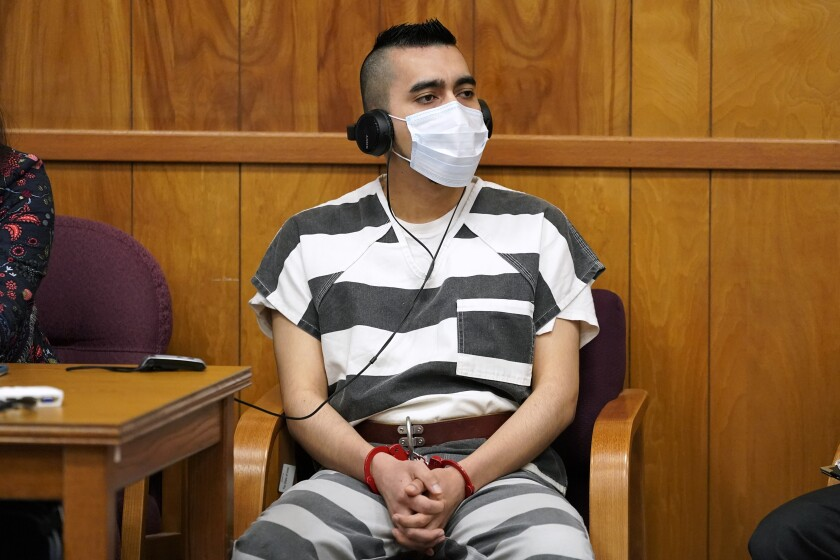 A man in prison garb, headphones and a mask sits in a chair.