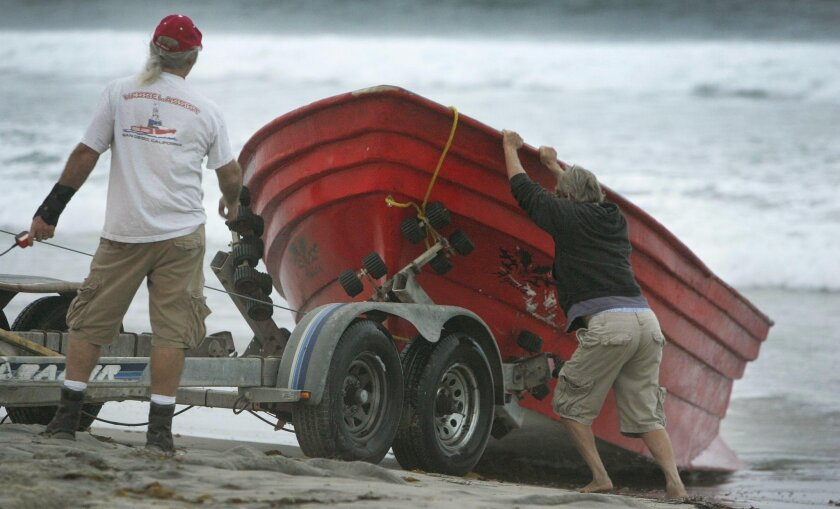 Crews work to remove a panga boat from the beach near Santa Barbara Place and Ocean Front Walk in Mission Beach early October 4, 2010, after at least 20 suspected illegal immigrants were arrested as they came ashore on the boat at about 2:30 a.m.