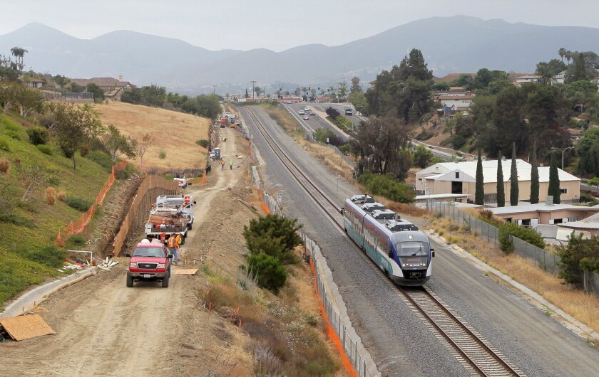 A westbound Sprinter train passes by construction of a mile-long segment of the Inland Rail Trail, shown at left. It will be paved when completed, and open to the public sometime in late summer. This view is looking east from the Las Flores Drive bridge in San Marcos.
