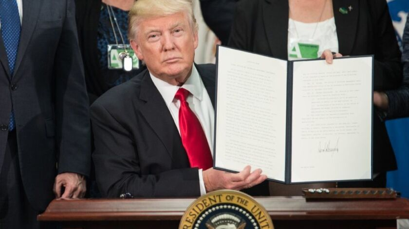 Donald Trump displays one of his executive orders.