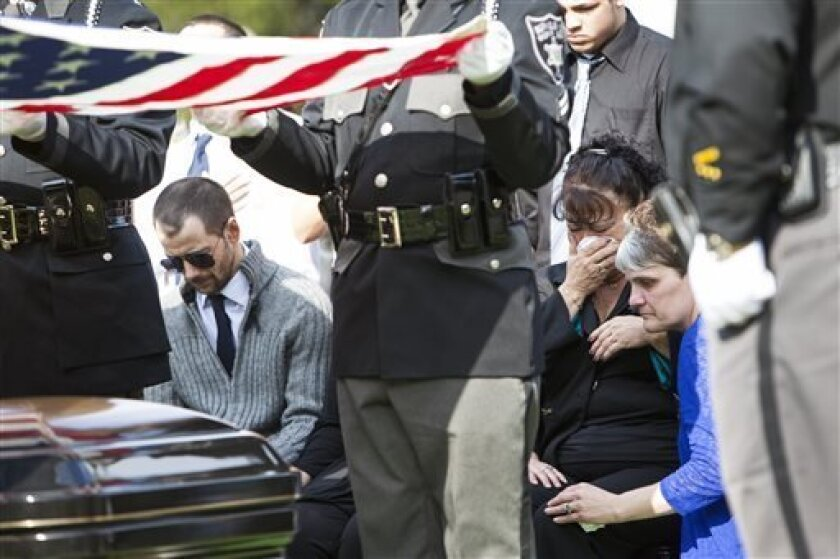 """Eugene """"Bub"""" Crum, left, bows his head as Lynette Morrison, right, comforts his mother Rosie Crum on Sunday, April 7, 2013, at Lenore Memorial Gardens in Lenore, W.Va. Law enforcement officials, family, friends and community leaders gathered for the burial service for the late Mingo County Sheriff"""