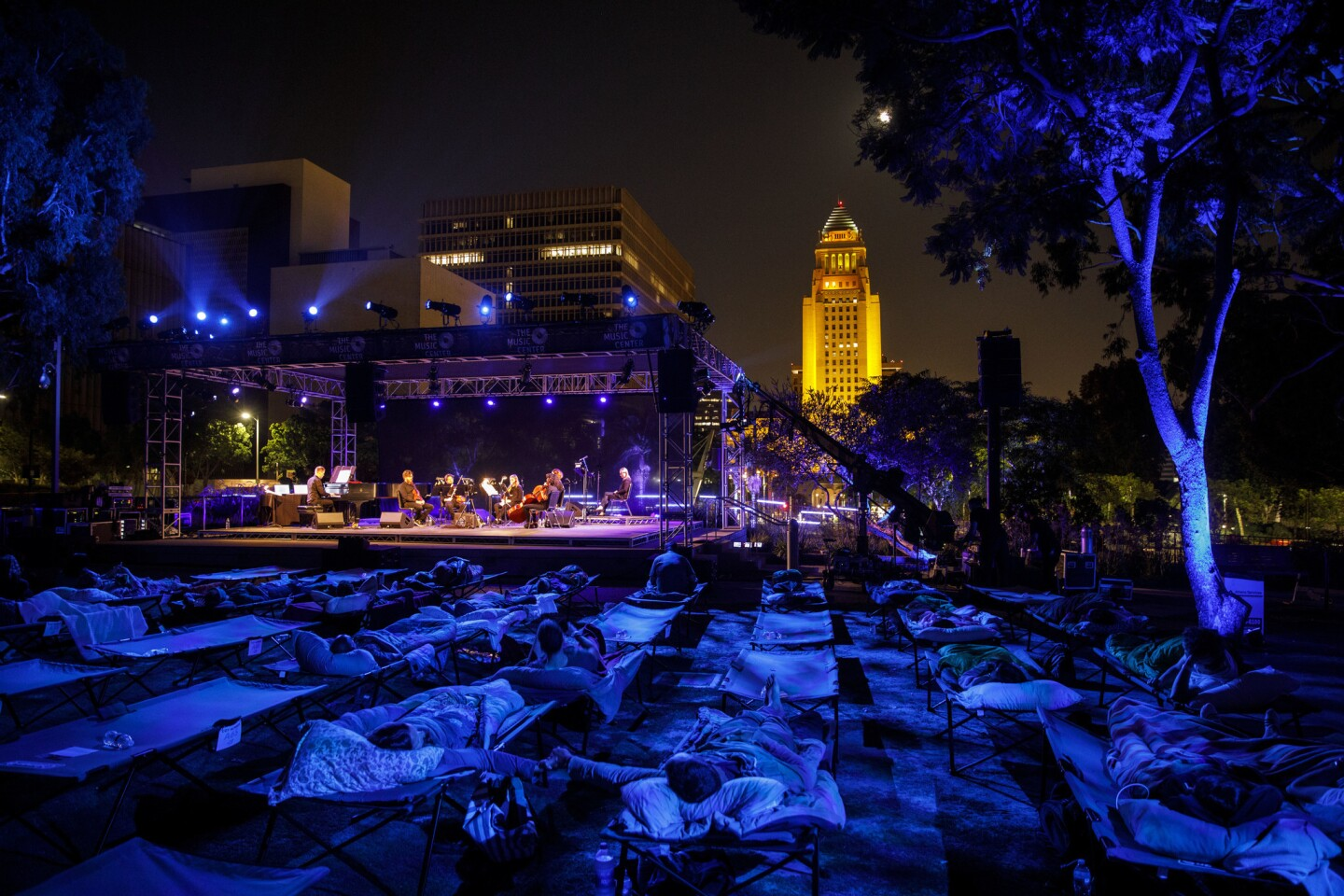 """Max Richter performs """"Sleep"""" as people lie in cots during a performance in Grand Park on Saturday, while L.A. City Hall is illuminated in gold to honor the late Los Angeles Times food critic Jonathan Gold."""