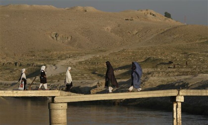 Afghan women and schoolgirls walk over a temporary bridge to cross a canal in Jalalabad, the provincial capital of Nangarhar province, east of Kabul, Afghanistan, Monday, Nov. 1, 2010. (AP Photo/Rahmat Gul)