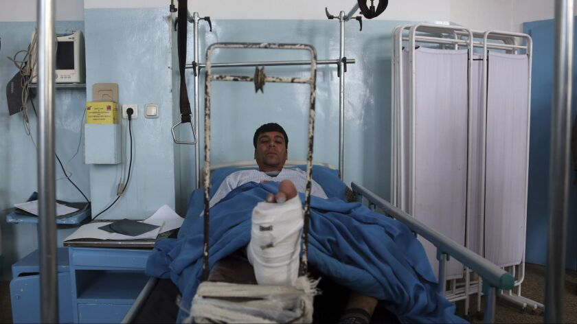 An Injured man receive treatment at a hospital after Monday's Christmas Eve attack, in Kabul, Afghan