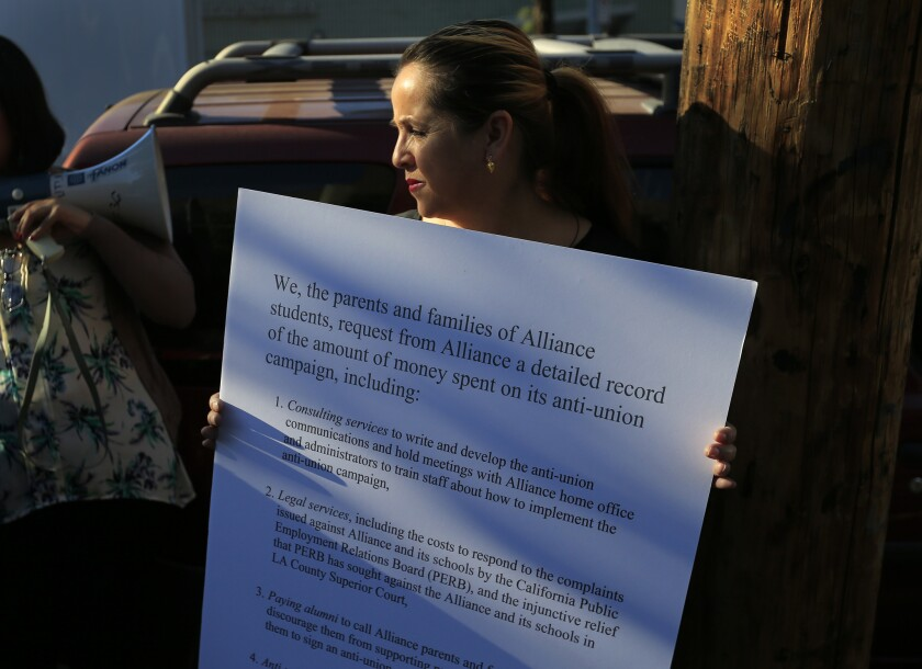 Maria Esparza of Huntington Park, shown outside Alliance Gertz-Ressler Academy High School in Los Angeles last November, holds up a sign detailing parents' concerns about Alliance's handling of unionization efforts.