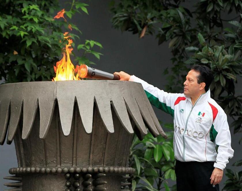 El exatleta mexicano Daniel Aceves Villagrán sostiene la llama olímpica hoy, viernes 12 de octubre de 2018, en el Estadio Olímpico Universitario, en Ciudad de México (México), durante las celebración del 50 Aniversario de los Juegos Olímpicos de México 1968. EFE