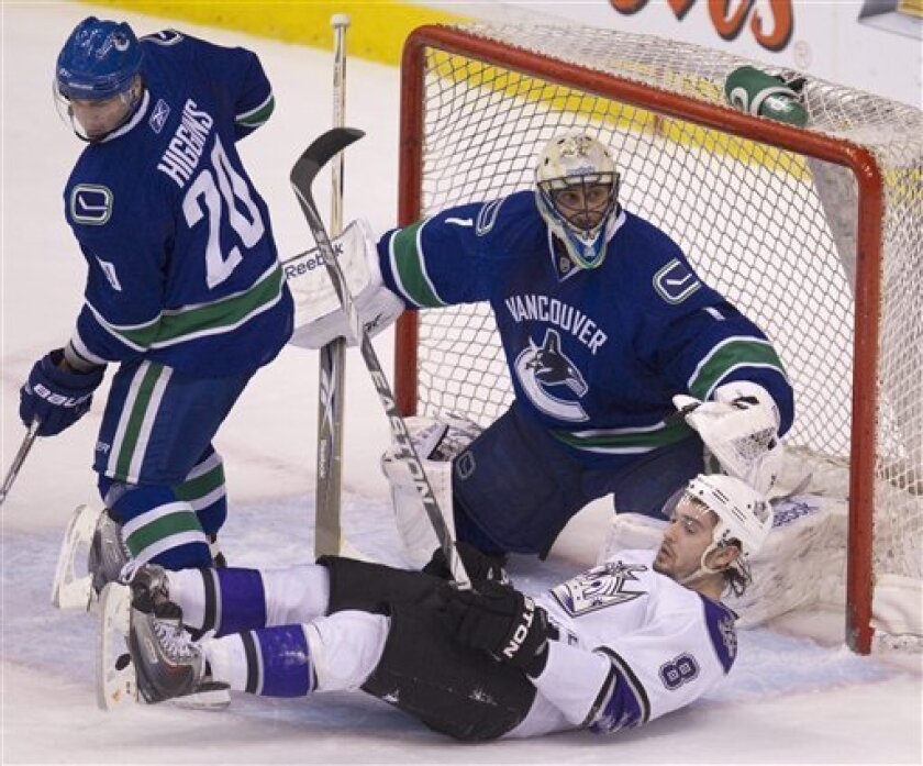 Los Angeles Kings defenseman Drew Doughty (8) crashes in front of Vancouver Canucks goalie Roberto Luongo (1) as he tries to get a shot on net as Canucks' Chris Higgins looks on during first period NHL hockey action at Rogers arena in Vancouver, British Columbia Thursday, March 31, 2011.  (AP Photo