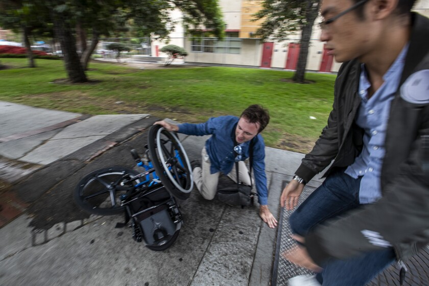 A passerby, right, rushes in to help after David Radcliff took a tumble while crossing a section of broken sidewalk on Jefferson Boulevard in his wheelchair.