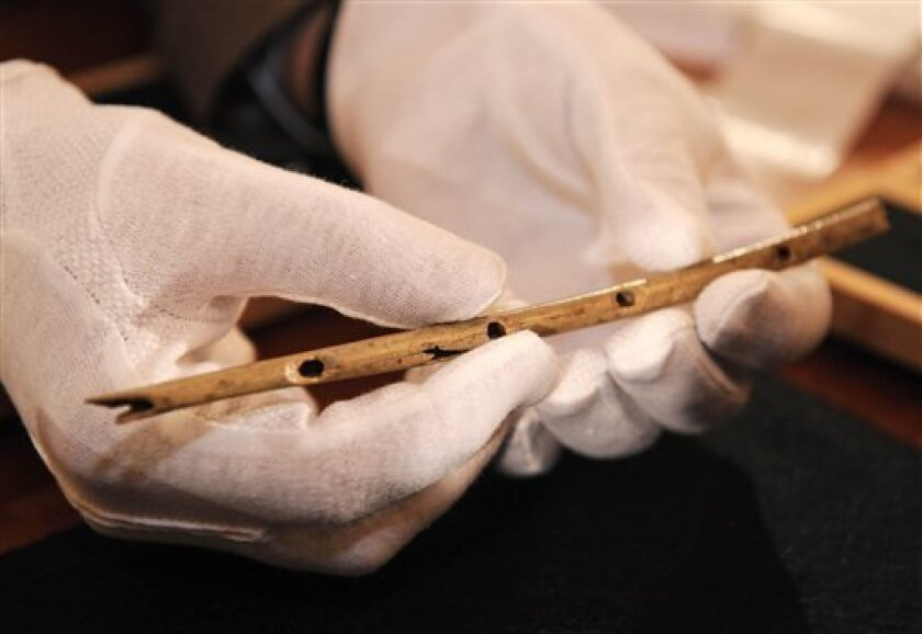 Professor Nicholas Conard of the University in Tuebingen shows a flute during a press conference in Tuebingen, southern Germany, on Wednesday, June 24, 2009. The thin bird-bone flute carved some 35,000 years ago and unearthed in a German cave is the oldest handcrafted musical instrument yet discovered, archeologists say, and offers the latest evidence that early modern humans in Europe had established a complex and creative culture. A team led by Conard assembled the flute from 12 pieces of griffon vulture bone scattered in a small plot of the Hohle Fels cave in southern Germany. (AP Photo/Daniel Maurer)