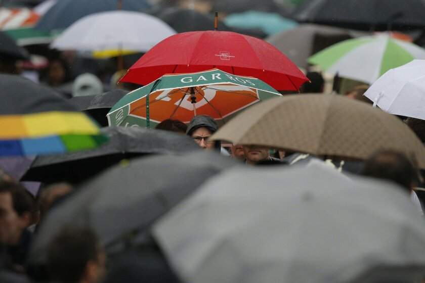 Spectators with umbrellas leave the courts as rain interrupted first round matches of the French Open tennis tournament at Roland Garros stadium in Paris, France, Sunday, May 22, 2016. (AP Photo/Christophe Ena)