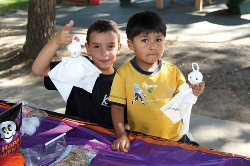 Ben and Christopher hold up handmade ghost. Photos by Jon Clark