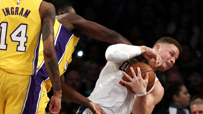Clippers forward Blake Griffin tries to protect the ball from the reach of Lakers forward Julius Randle during the first half.