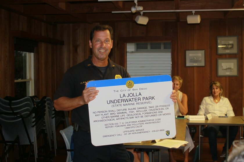 San Diego lifeguard Lt. Rich Stropky with a mock-up of a sign lifeguards plan to post at the boat launch at La Jolla Shores, which he showed as part of his summer wrap-up.