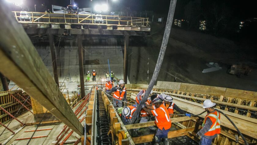 SAN DIEGO, CA December 21st, 2017 | Construction crews pour cement during at nighttime operation at