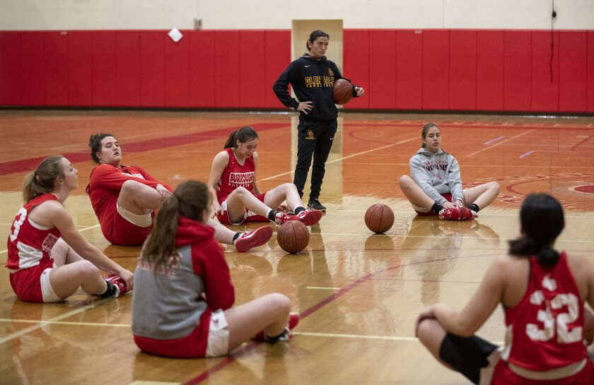 Burroughs girls basketball coach Vicky Oganyan stands while her team stretches for a late evening practice in the school gym on Feb. 12.