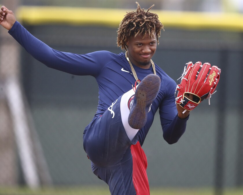 Atlanta Braves outfielder Ronald Acuna Jr. kicks up his heels while loosening up at spring training baseball camp in North Port, Fla., Wednesday, Feb. 12, 2020.